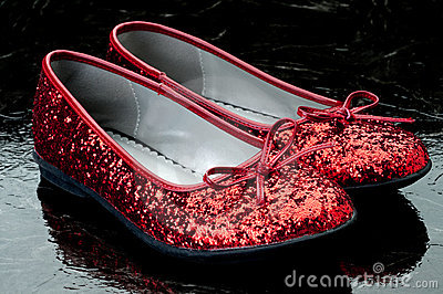 Sequined red slippers on dark tile.