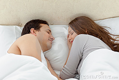 Serene couple sleeping together on their bed