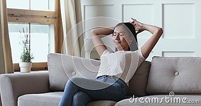 Serene jonge aziatische vrouw die op de bank rust, zit op de bank stock footage