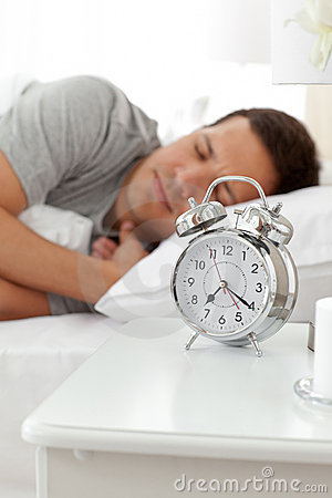 Serene man lying on his bed before being woken up