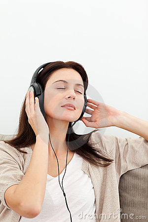 Serene woman listening to the music on the sofa