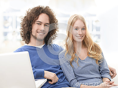 Serene young smiling couple with laptop
