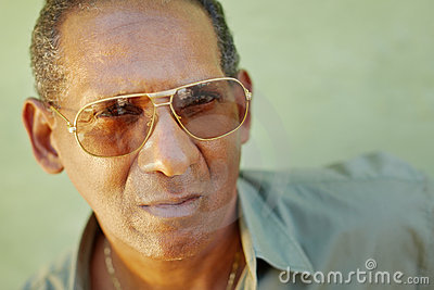 Serious aged man with sunglasses looking at camera