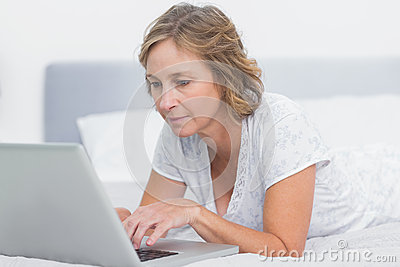 Serious blonde woman lying on bed using laptop