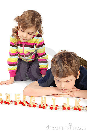 Serious boy and girl playing with wooden railway