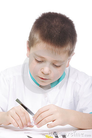 Serious boy with magnifier and tweezers
