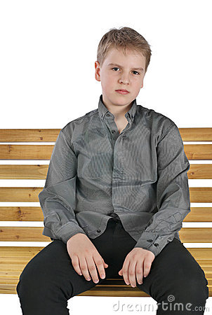 Serious boy sitting on a bench