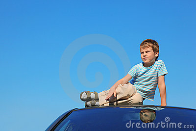 Serious boy sitting on roof of car