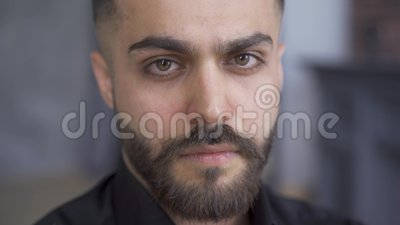 Serious brunette man with beard and mustaches looking at the camera. Portrait of attractive caucasian man in black shirt.  stock video