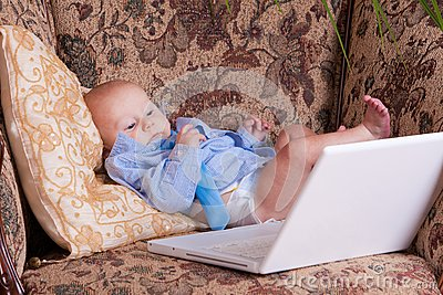 Serious business baby near computer on sofa