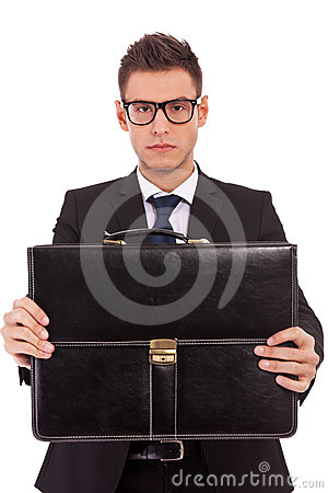 Serious business man offering a briefcase