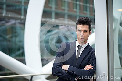 Serious businessman with arms crossed outdoors
