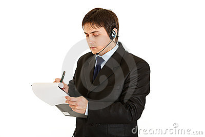 Serious businessman making notes in document