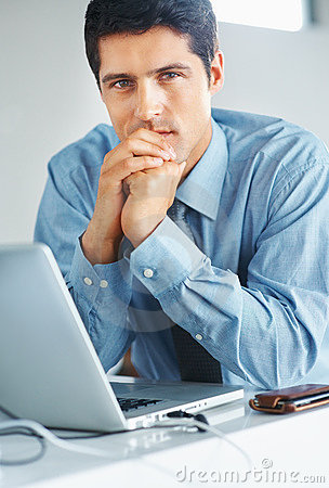 Serious businessman sitting in front of laptop