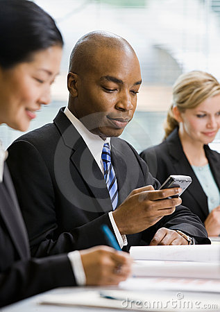 Serious businessman text messaging on cell phone