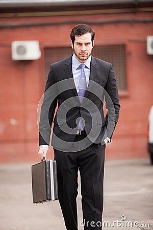 Serious businessman walking on the street