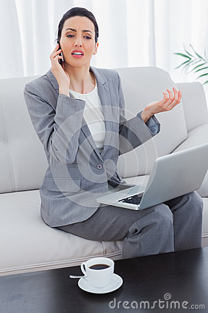 Serious businesswoman calling with her mobile phone and using laptop sitting on sofa