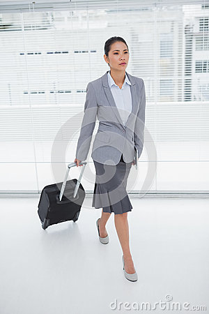 Serious businesswoman carrying her suitcase
