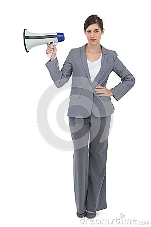 Serious businesswoman holding loudspeaker
