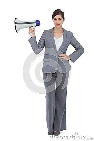 Serious businesswoman holding loudspeaker