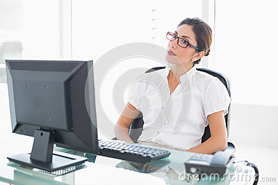 Serious businesswoman sitting at her desk looking at computer
