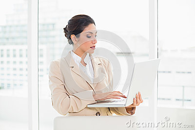 Serious businesswoman standing behind her chair holding laptop