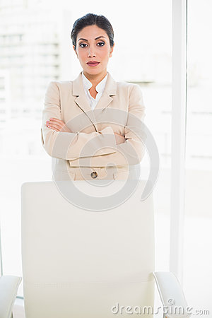 Serious businesswoman standing behind her chair