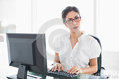 Serious businesswoman working at her desk looking at camera