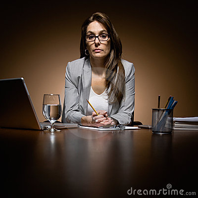 Serious businesswoman working late at desk