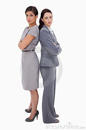 Serious businesswomen standing back on back