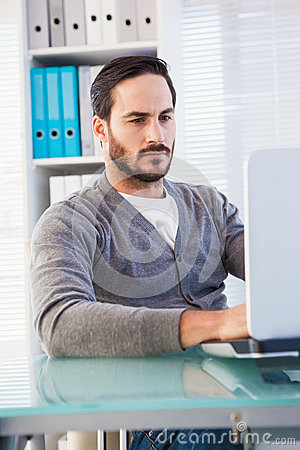 Serious casual businessman working on laptop at his desk Stock Photo