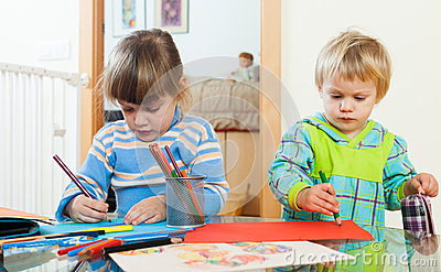 Serious children drawing with pencils Stock Photo