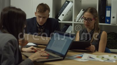Serious colleagues analyzing documents on tablet stock video footage