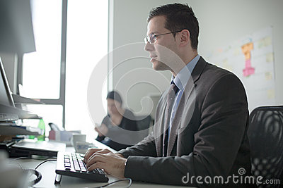 Serious devoted business man work in office on computer. Real economist business people, not models. Bank employees discussing Stock Photo