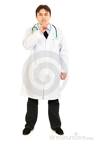 Serious doctor with finger at mouth. Shh gesture