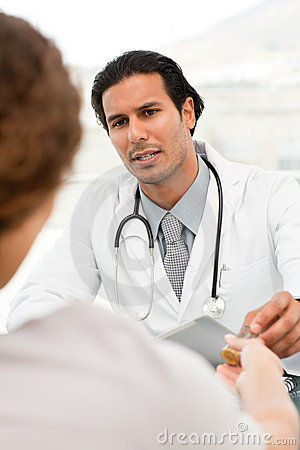 Serious doctor giving pills to his patient