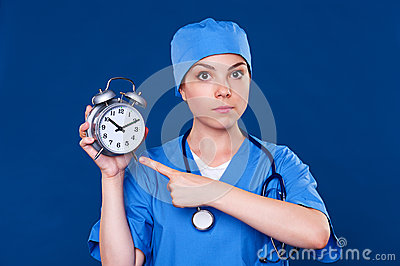 Serious doctor pointing at alarm clock