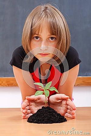 Serious elementary schoolgirl protecting plant