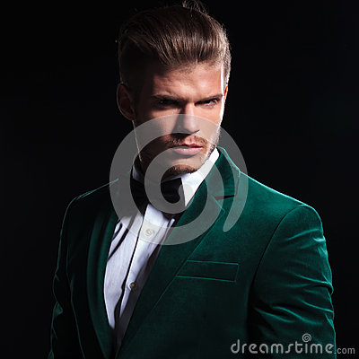 Serious face of a young man wearing green velvet suit