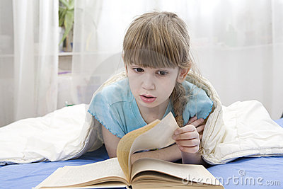 Serious girl reading a book lying in bed