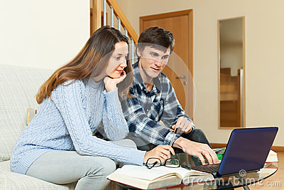 Serious guy and girl preparing for exam with laptop