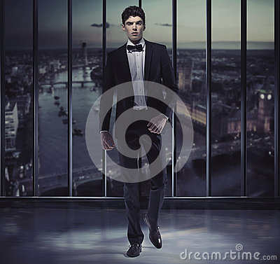 Serious handsome man on the top of the skyscraper