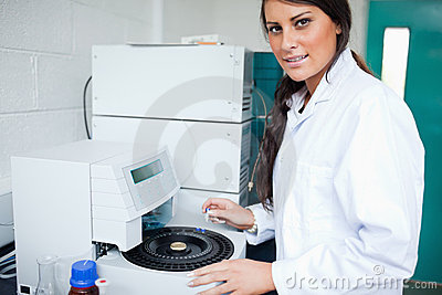 Serious laboratory assistant using a centrifuge