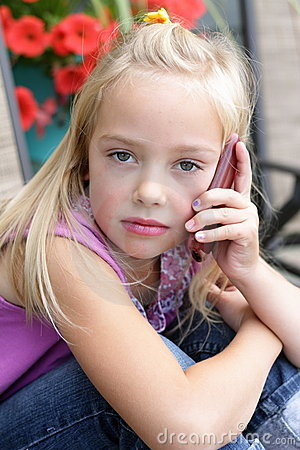 Serious little blond girl talking on a cellphone