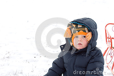 Serious little boy in winter snow