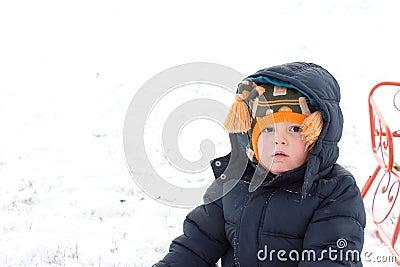 Serious little boy in winter snow