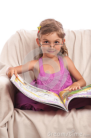 Serious little girl in glasses with big book