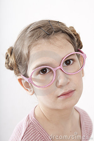 Serious little girl nine years old in pink glasses