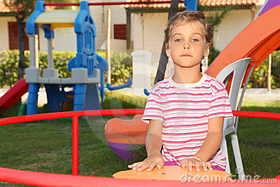Serious little girl sitting on merry-go-round