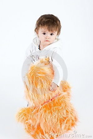 Serious looking girl standing with big orange furr